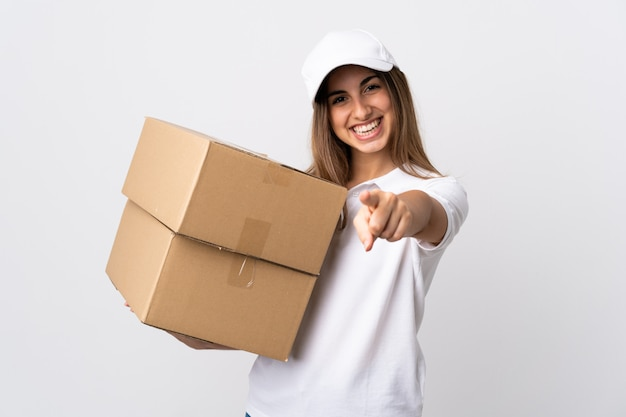 Young delivery woman over isolated white background pointing front with happy expression