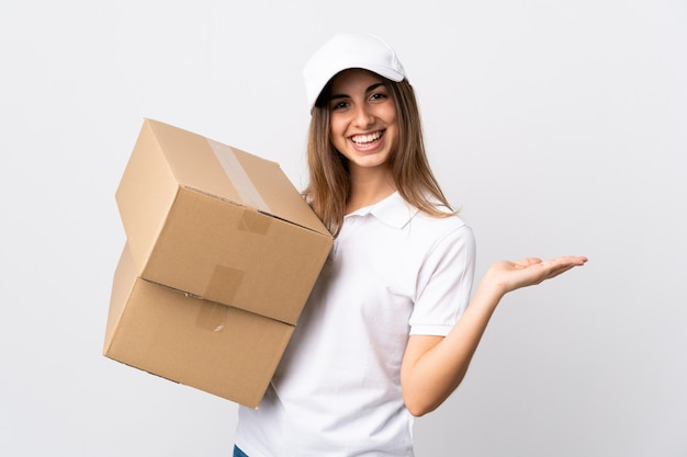 Young delivery woman over isolated white background presenting an idea while looking smiling towards