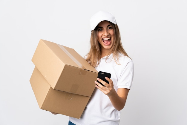 Young delivery woman over isolated white background surprised and sending a message