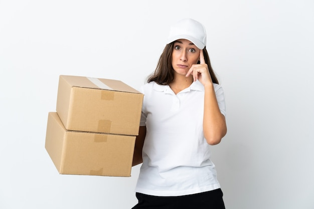 Young delivery woman over isolated white background thinking an idea