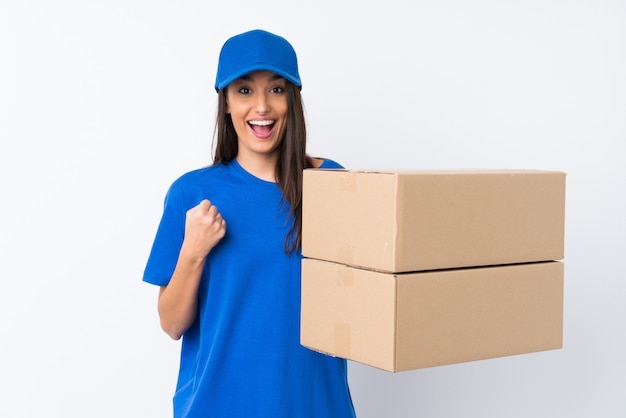 Young delivery woman over isolated white wall celebrating a victory