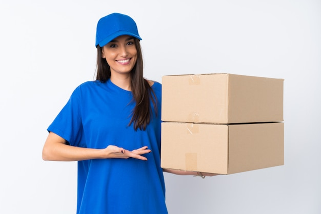 Young delivery woman over isolated white wall extending hands to the side for inviting to come