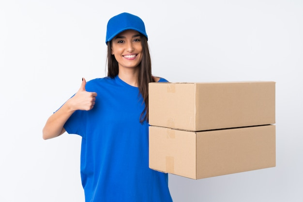 Young delivery woman over isolated white wall giving a thumbs up gesture
