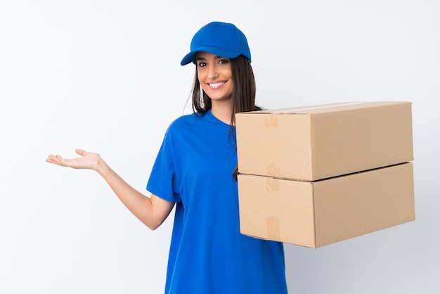 Young delivery woman over isolated white wall holding copyspace imaginary on the palm
