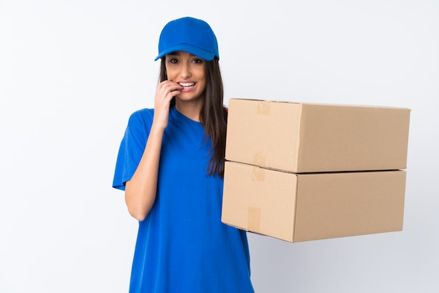 Young delivery woman over isolated white wall nervous and scared