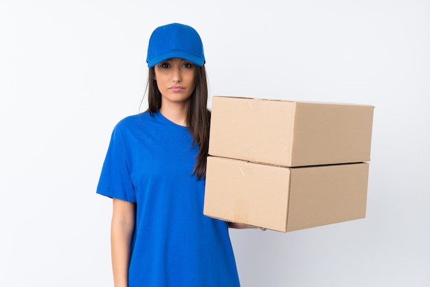 Young delivery woman over isolated white wall sad