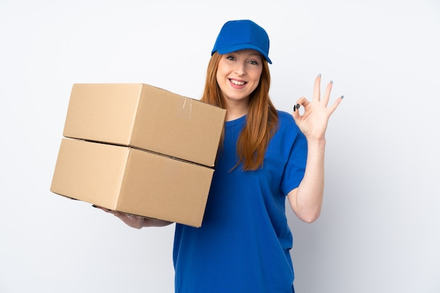 Young delivery woman over isolated white wall showing an ok sign with fingers