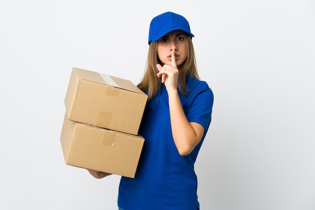 Young delivery woman over isolated white wall showing a sign of silence gesture putting finger in mouth