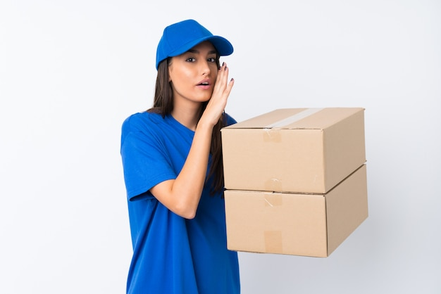 Young delivery woman over isolated white wall whispering something