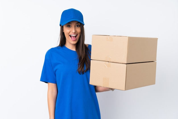 Young delivery woman over isolated white wall with surprise facial expression