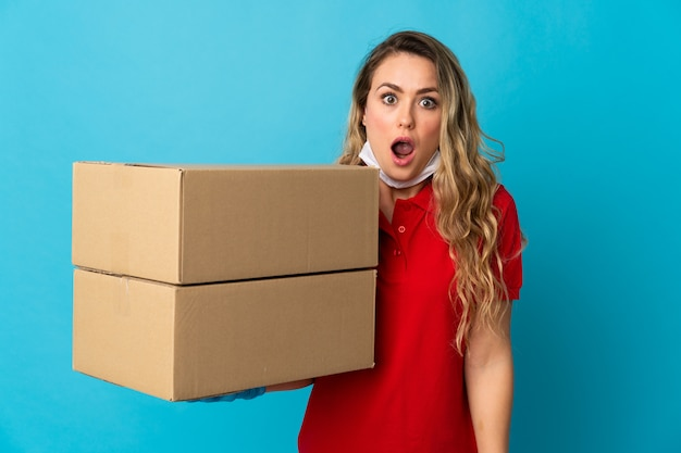 Young delivery woman isolated on white with surprise and shocked facial expression