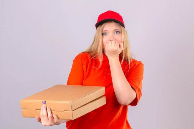 Young delivery woman in orange polo shirt and red cap holding a stack of pizza boxes looking stressed and nervous with hands on mouth biting nails over isolated white background