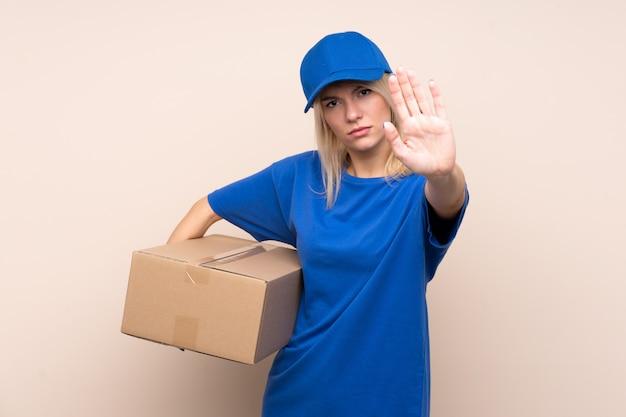 Молодая женщина доставки через изолированную стену, делая остановки жест рукой