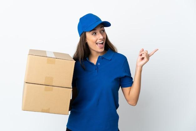 Молодая женщина-доставщик на изолированном белом фоне, намереваясь реализовать решение, подняв палец вверх