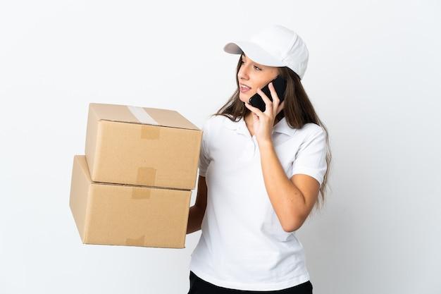 Молодая женщина доставки на изолированном белом фоне, поддерживая разговор с кем-то по мобильному телефону
