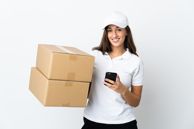 Молодая женщина доставки на изолированном белом фоне, отправив сообщение с мобильного телефона