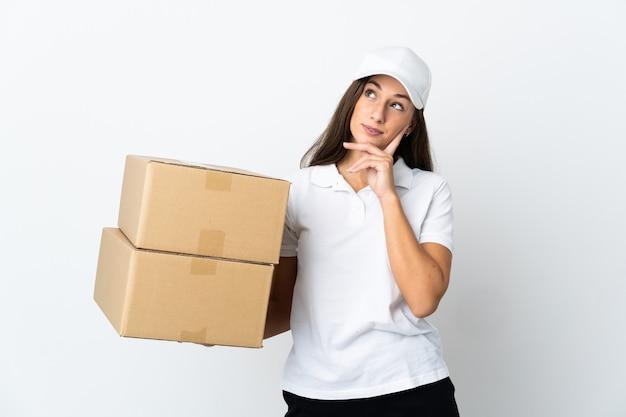Молодая женщина доставки на изолированном белом фоне, думая об идее, глядя вверх