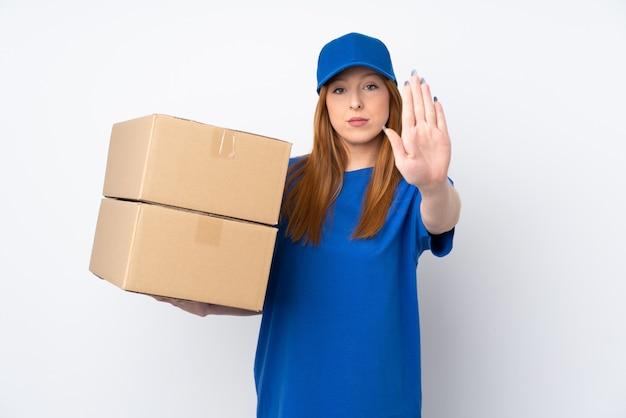 Молодая женщина доставки на изолированной белой стене, делая остановки жест рукой