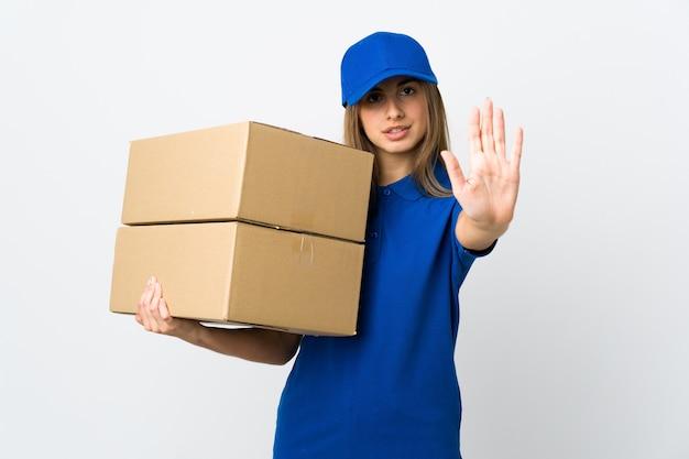 Молодая женщина-доставщик над изолированной белой стеной делает стоп-жест