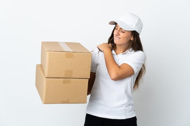 Молодая женщина-доставщик над изолированной белой стеной страдает от боли в плече из-за того, что приложила усилие