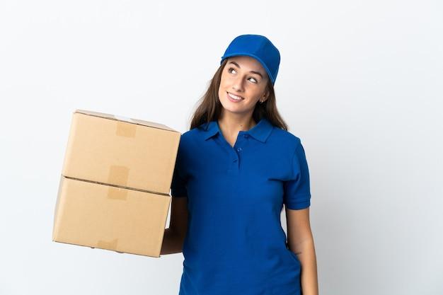 Молодая женщина-доставщик над изолированной белой стеной думает об идее, глядя вверх