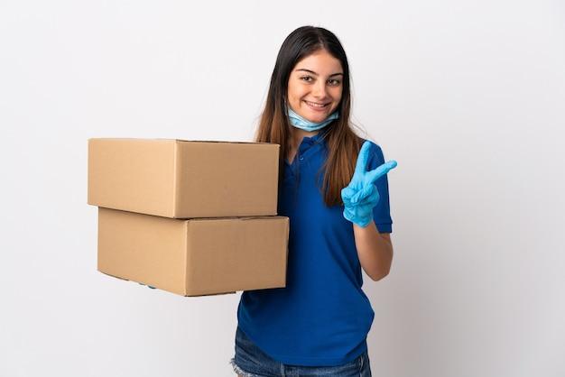 Молодая женщина-доставщик, защищающая от коронавируса с маской, изолированной на белой стене, улыбается и показывает знак победы