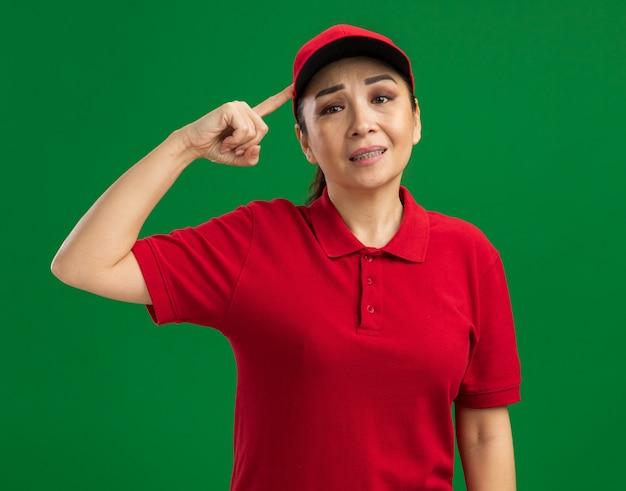 Giovane donna delle consegne in uniforme rossa e berretto confuso e dispiaciuto che indica con il dito indice alla testa in piedi sul muro verde green