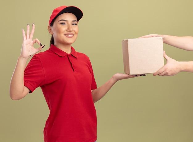 Giovane donna di consegna in uniforme rossa e cappuccio che dà la scatola di cartone ad un cliente che sorride amichevole che mostra segno giusto che sta sopra la parete verde