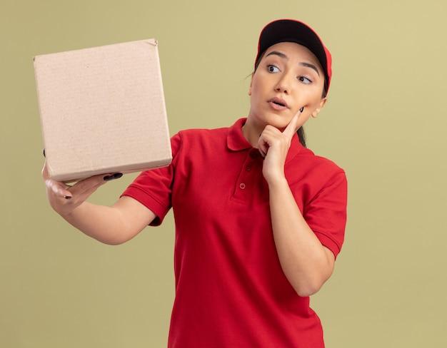 Giovane donna di consegna in uniforme rossa e cappuccio che tiene la scatola di cartone guardandolo con espressione pensierosa pensando in piedi sopra la parete verde