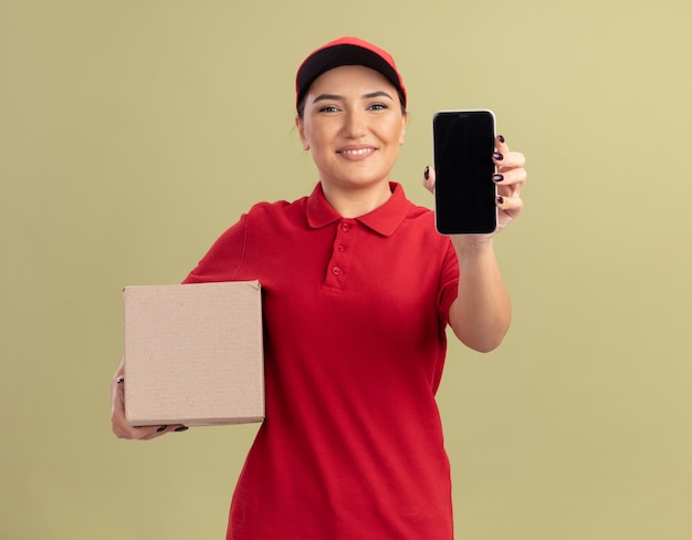 Giovane donna delle consegne in uniforme rossa e cappuccio che tiene la scatola di cartone che mostra smartphone guardando davanti con il sorriso sul viso in piedi sopra la parete verde