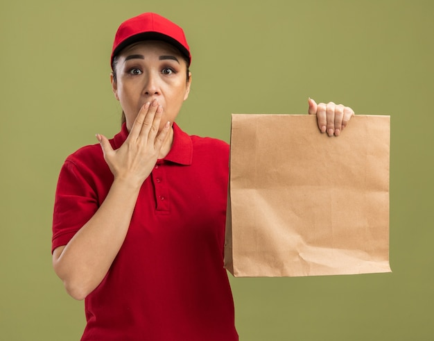 Giovane donna delle consegne in uniforme rossa e cappuccio che tiene un pacchetto di carta scioccata che copre la bocca con la mano