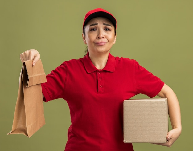 Young delivery woman in red uniform and cap holding paper package and cardboard box  being confused and displeased standing over green wall