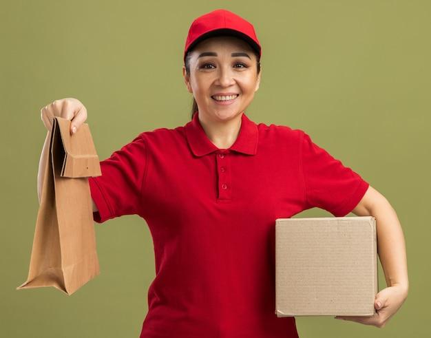 Giovane donna delle consegne in uniforme rossa e cappuccio che tiene in mano un pacchetto di carta e una scatola di cartone sorridente amichevole