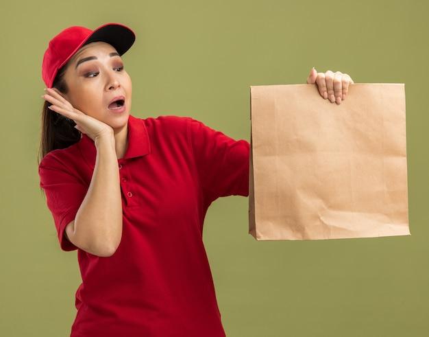 Giovane donna delle consegne in uniforme rossa e berretto che tiene un pacchetto di carta guardandolo stupito e sorpreso