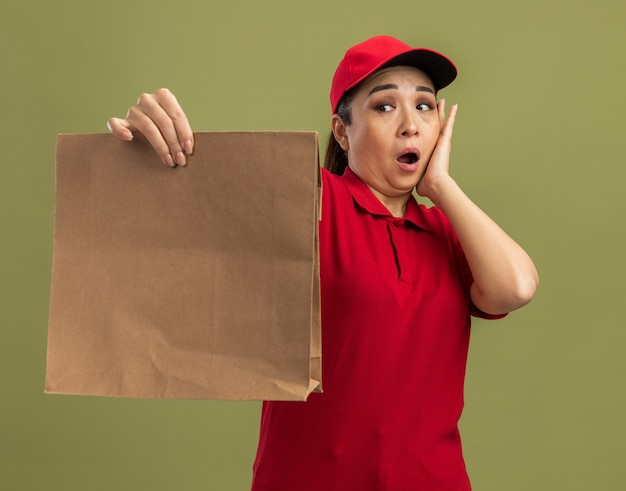 Young delivery woman in red uniform and cap holding paper package looking at it confused and surprised standing over green wall