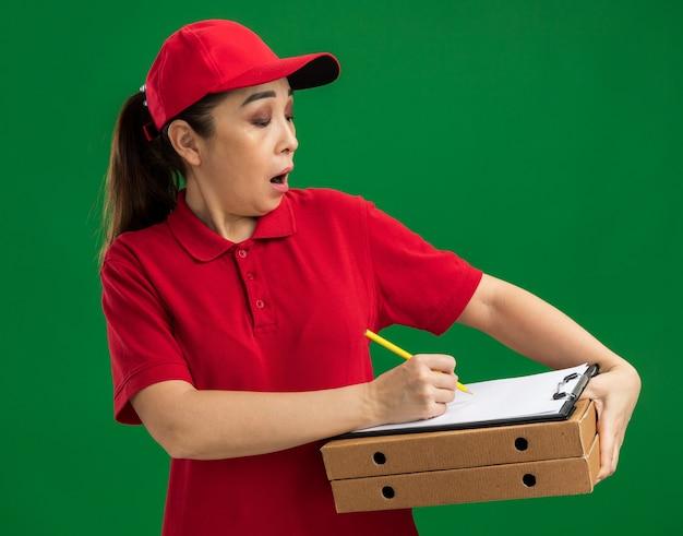 Giovane donna delle consegne in uniforme rossa e berretto con scatole per pizza e appunti con penna che scrive qualcosa di sorpresa