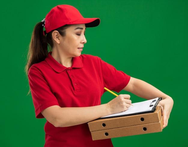 Giovane donna delle consegne in uniforme rossa e berretto che tiene scatole per pizza e appunti con penna che scrive qualcosa con espressione sicura