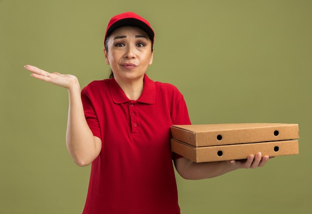 Giovane donna delle consegne in uniforme rossa e berretto che tiene scatole di pizza confuse con il braccio alzato in piedi sul muro verde green