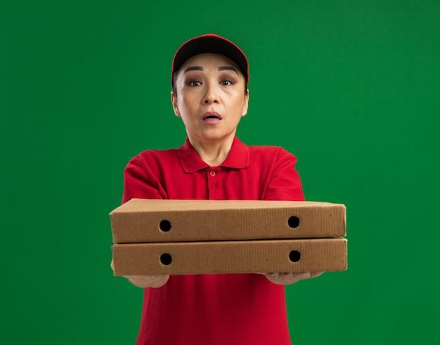 Giovane donna delle consegne in uniforme rossa e berretto che tiene in mano scatole per pizza confuse
