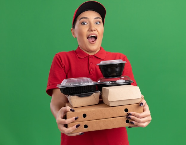 Giovane donna di consegna in uniforme rossa e cappuccio che tiene scatole di pizza e confezioni di cibo guardando davanti stupito e sorpreso in piedi sopra la parete verde