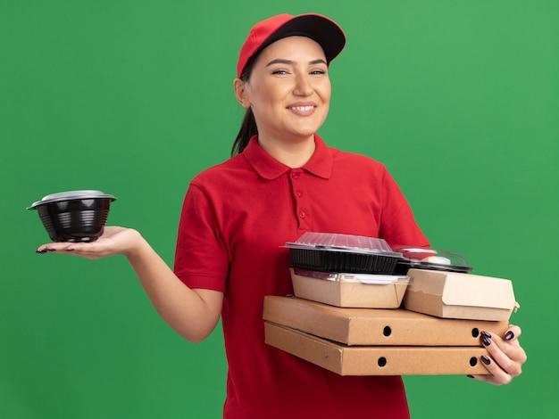 Giovane donna delle consegne in uniforme rossa e cappuccio che tiene scatole di pizza e pacchetti di cibo guardando la parte anteriore sorridente allegramente in piedi sopra la parete verde