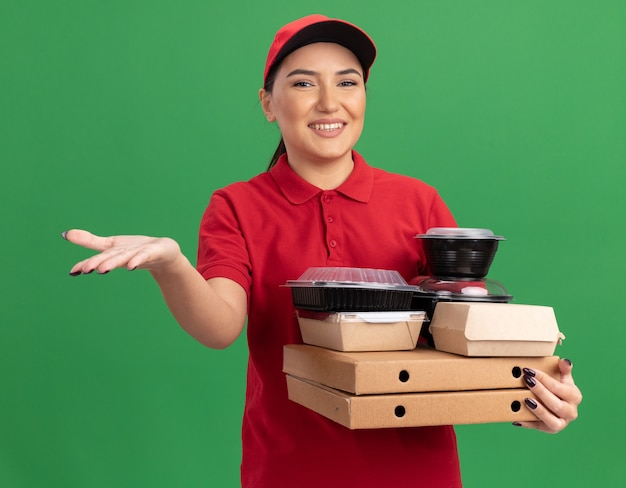 Giovane donna delle consegne in uniforme rossa e cappuccio che tiene scatole di pizza e confezioni di cibo guardando la parte anteriore con il sorriso sul viso con il braccio alzato che fa gesto di benvenuto in piedi sopra la parete verde