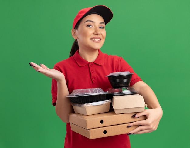 Giovane donna delle consegne in uniforme rossa e cappuccio che tiene scatole per pizza e confezioni di cibo guardando davanti con il sorriso sul viso con il braccio alzato in piedi sopra la parete verde