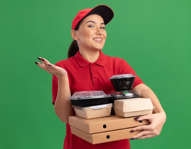 Young delivery woman in red uniform and cap holding pizza boxes and food packages looking at front with smile on face with arm raised standing over green wall