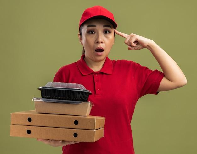 Giovane donna delle consegne in uniforme rossa e berretto che tiene in mano scatole di pizza e pacchi di cibo che punta con il dito indice alla tempia e sembra sorpresa in piedi sul muro verde green