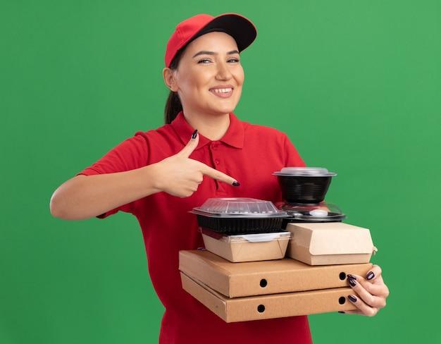 Giovane donna delle consegne in uniforme rossa e cappuccio che tiene scatole di pizza e confezioni di cibo che punta con il dito indice a loro sorridendo allegramente in piedi sopra la parete verde