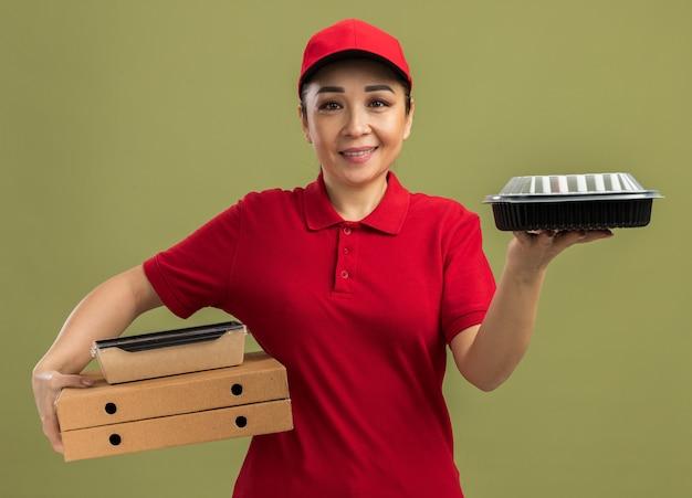 Giovane donna delle consegne in uniforme rossa e berretto che tiene scatole per pizza e confezioni di cibo con un sorriso sul viso in piedi sul muro verde