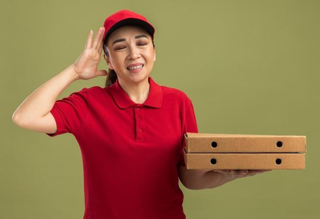 Giovane donna delle consegne in uniforme rossa e berretto che tiene in mano scatole per pizza che sembra infastidita e irritata con il braccio alzato in piedi sul muro verde