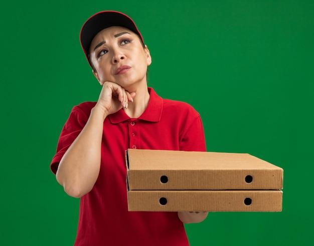 Giovane donna delle consegne in uniforme rossa e berretto che tiene in mano scatole per pizza alzando lo sguardo perplesso