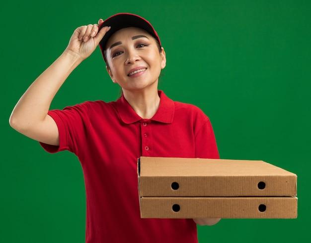 Giovane donna delle consegne in uniforme rossa e berretto che tiene in mano scatole per pizza sorridenti fiduciose